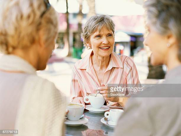 Close-up of three mature women sitting and talking