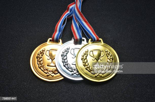 Close-Up Of Three Medals Against Black Background