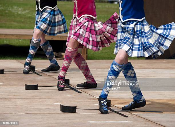 closeup of three pairs of feet of women scottish sword dancing - kilt stock photos and pictures