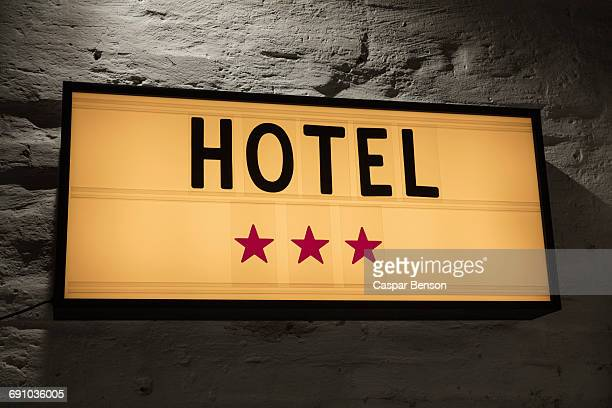 Close-up of Three Stars Hotel signboard against gray wall