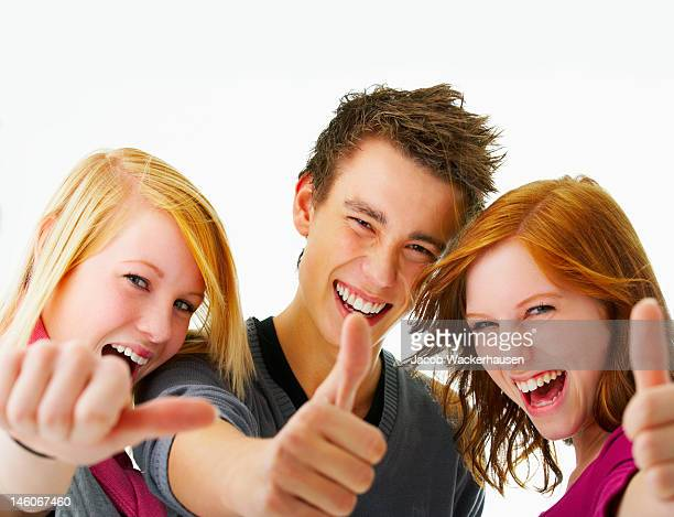Close-up of three teenagers laughing and gesturing thumbs-up sign