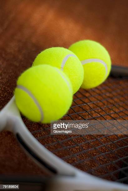 Close-up of three tennis balls on a tennis racket