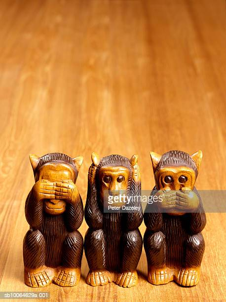 close-up of three wooden monkey statues on table - see no evil hear no evil speak no evil stock pictures, royalty-free photos & images