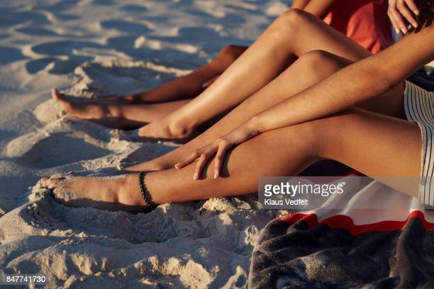 Close-up of three young womens legs, on sandy beach