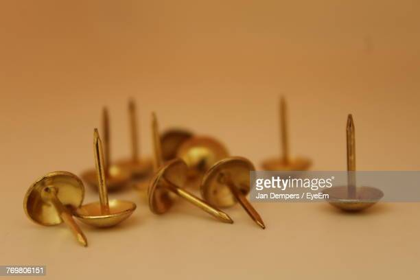 Close-Up Of Thumbtacks On Table