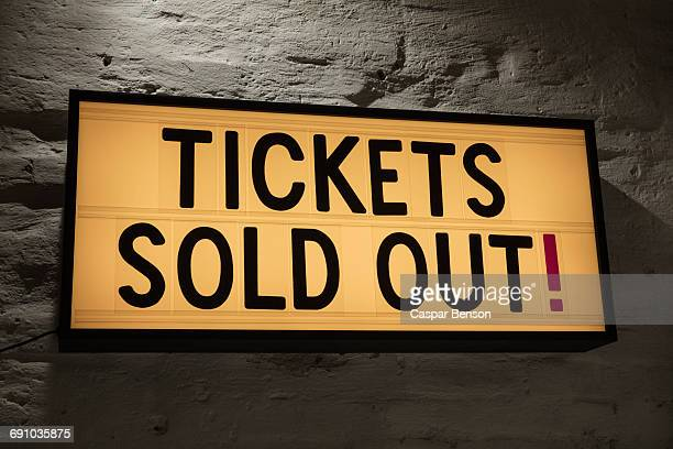 Close-up of Tickets Sold Out signboard against gray wall