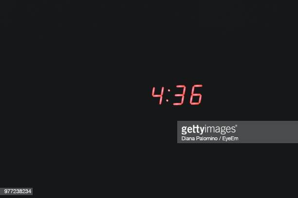 close-up of time against black background - digital clock stock photos and pictures