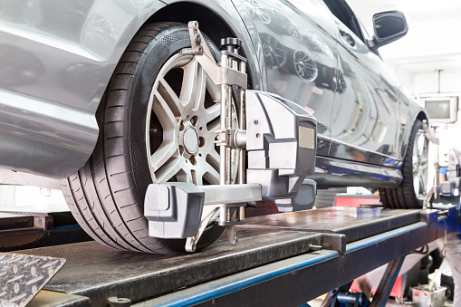 Closeup of tire clamped with aligner undergoing auto wheel align 517080534