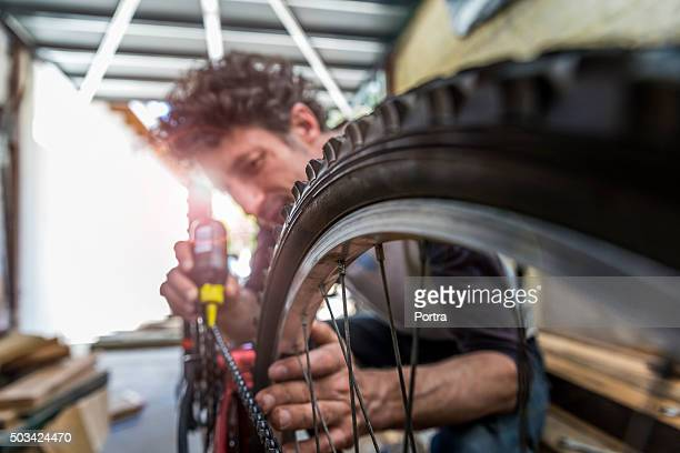 Nahaufnahme eines reifen mit ältere Mechaniker oiling Kette im Hintergrund