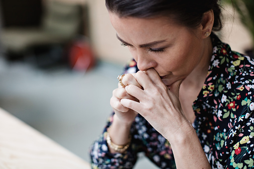 Close-up of tired thoughtful businesswoman with arms crossed at office - gettyimageskorea