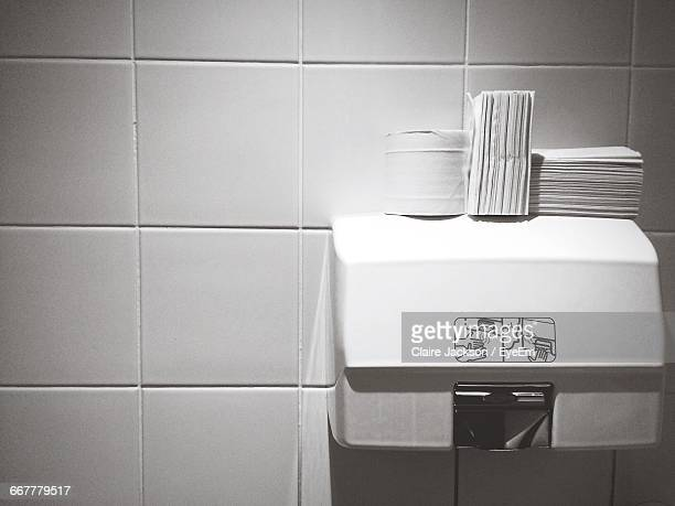 Close-Up Of Tissue Papers On Hand Dryers Against Tile Wall