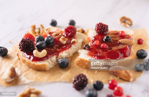 Close-up of toast with homemade strawberry jam on table - Stock image...