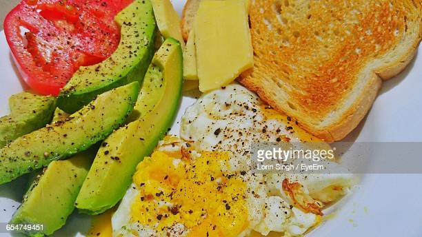 Close-Up Of Toasted Bread With Fruits Slices And Scrambled Eggs In Plate