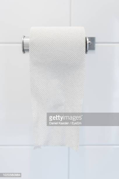 close-up of toilet paper hanging against white wall - クルクルと巻いた ストックフォトと画像