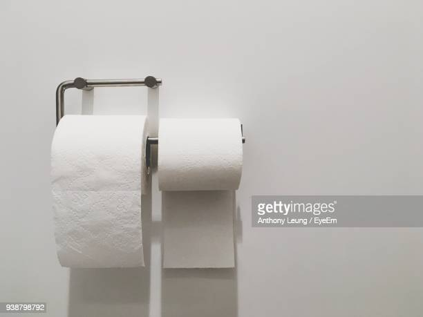close-up of toilet papers on white wall - position stock-fotos und bilder