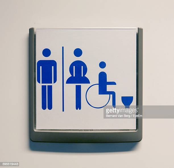 Close-Up Of Toilet Signs On Hospital Wall