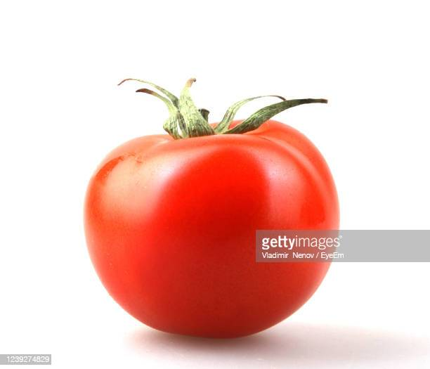 close-up of tomato against white background - tomato stock pictures, royalty-free photos & images