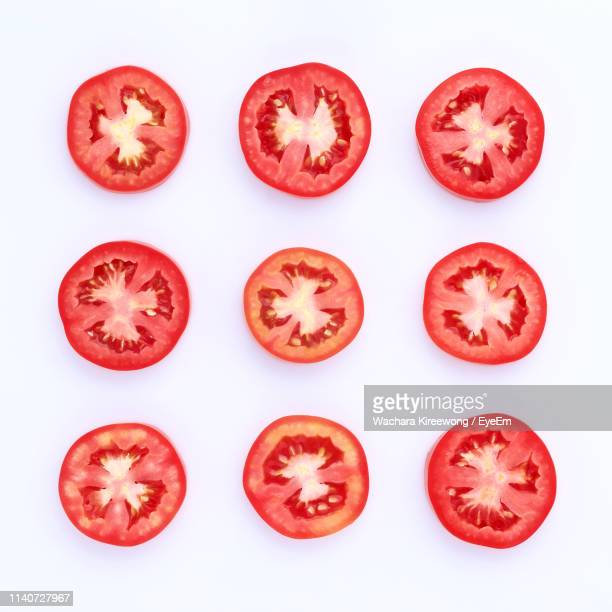 close-up of tomato slices against white background - cross section stock pictures, royalty-free photos & images