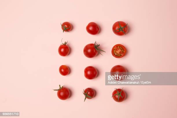 close-up of tomatoes against pink background - cherry tomato stock pictures, royalty-free photos & images