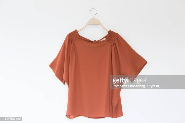 close-up of top hanging against gray background - womenswear stock pictures, royalty-free photos & images