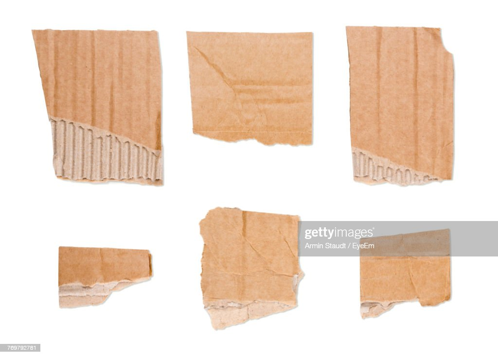 Close-Up Of Torn Brown Papers On White Background : Stock Photo