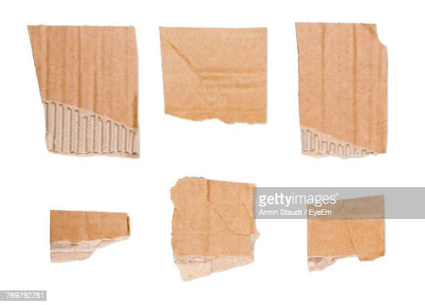 close-up of torn brown papers on white background - cardboard stock pictures, royalty-free photos & images