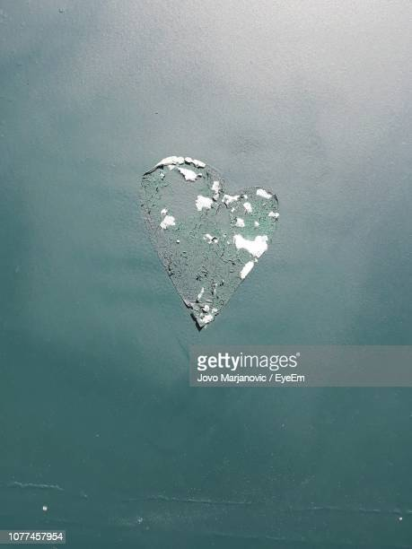 Close-Up Of Torn Heart Shaped Sticker On Green Wall