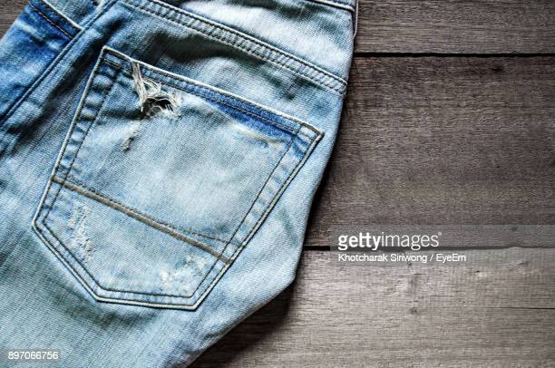 Close-Up Of Torn Jeans On Table