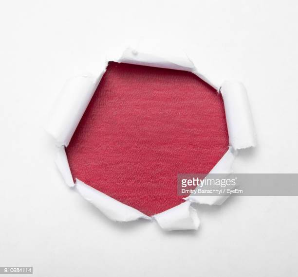 close-up of torn paper on red table - hole stock pictures, royalty-free photos & images