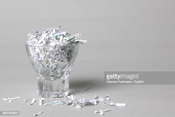 close-up of torn papers in drinking glass over gray background - shredded stock pictures, royalty-free photos & images