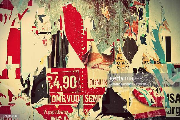 Close-Up Of Torn Posters On Wall