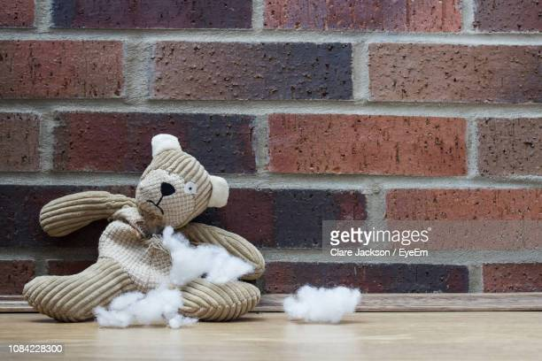 close-up of torn stuffed toy on wooden table by brick wall - soft toy stock pictures, royalty-free photos & images