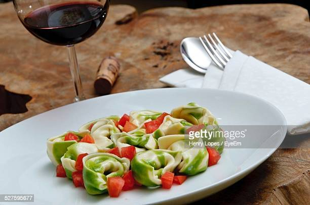Close-Up Of Tortellini Served With Red Wine On Table
