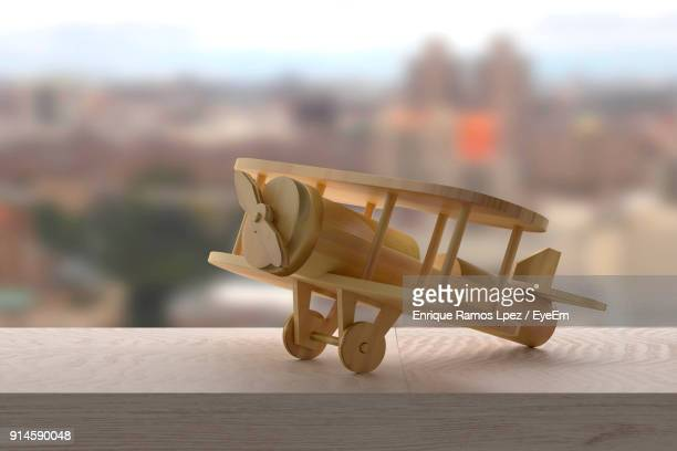 Close-Up Of Toy Airplane On Wooden Railing