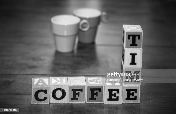 Close-Up Of Toy Blocks With Coffee Cups On Table