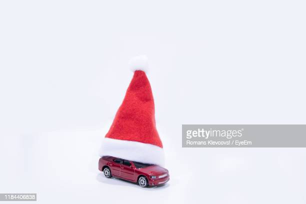close-up of toy car and santa hat against white background - santa close up stock pictures, royalty-free photos & images