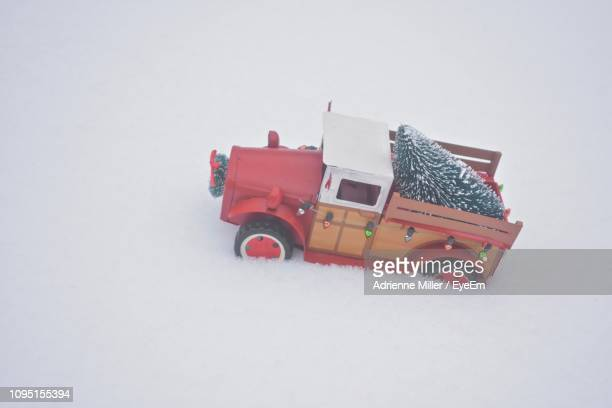 Close-Up Of Toy Car With Christmas Tree Figurine On Snow