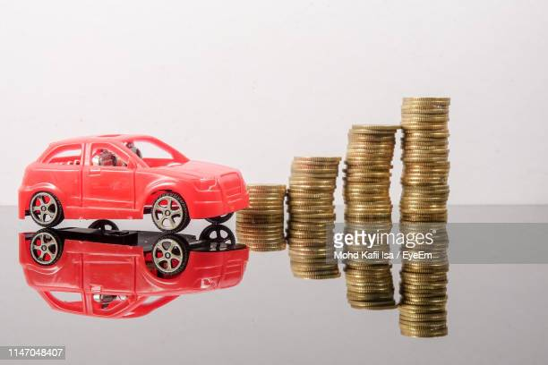 close-up of toy cars and coins on table against white background - car insurance stock pictures, royalty-free photos & images