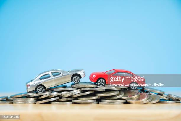 Close-Up Of Toy Cars On Coins Against Blue Wall