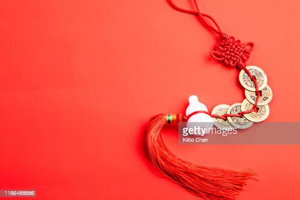 closeup of traditional chinese fengshui decorations against red background - oorhanger stockfoto's en -beelden