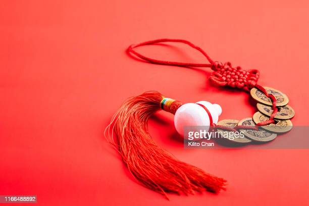 closeup of traditional chinese fengshui decorations against red background - chinese knotting stock pictures, royalty-free photos & images