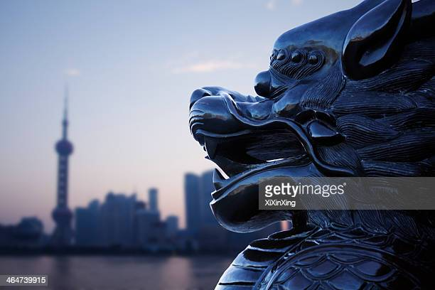 Close-up of traditional Chinese statue with Shanghai skyline in the background