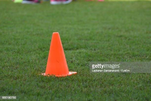 Close-Up Of Traffic Cone On Grassy Field
