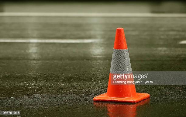 close-up of traffic cone on wet street - cone shape stock photos and pictures