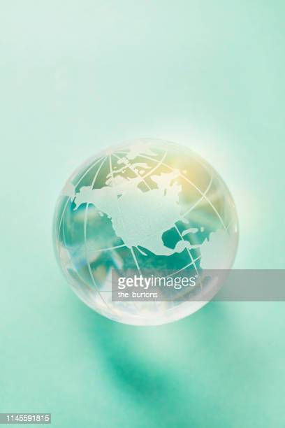 close-up of transparent globe on turquoise background - the americas stock pictures, royalty-free photos & images