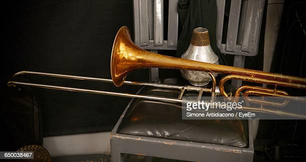 Close-Up Of Trombone And Container On Chair At Home