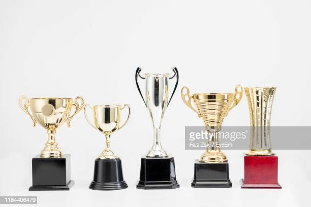 close-up of trophies against white background - trophy stock pictures, royalty-free photos & images