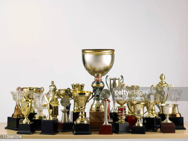 close-up of trophies on table against white background - トロフィー ストックフォトと画像