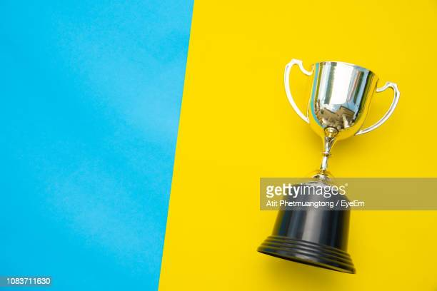 close-up of trophy against blue background - trofeo fotografías e imágenes de stock