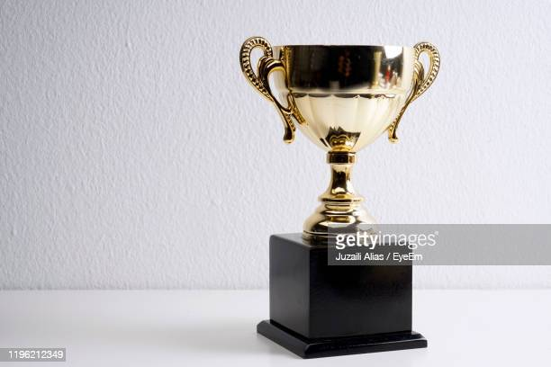 close-up of trophy against wall on table - trophy stock pictures, royalty-free photos & images